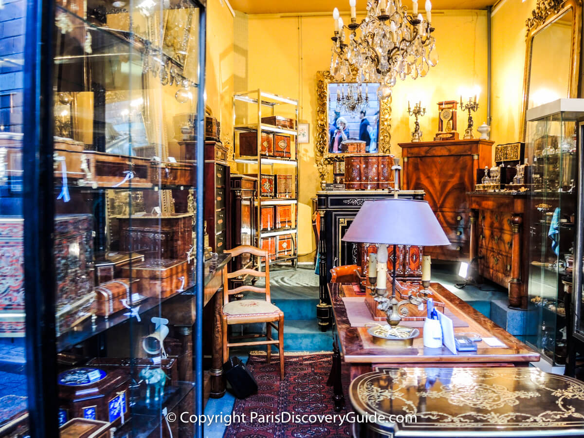 Inlaid boxes and fine furniture in antiques showroom at Paris Flea Market