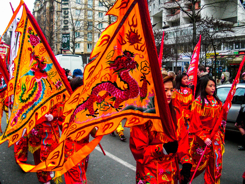 Marchers carrying flags in Paris Chinese New Year Parade