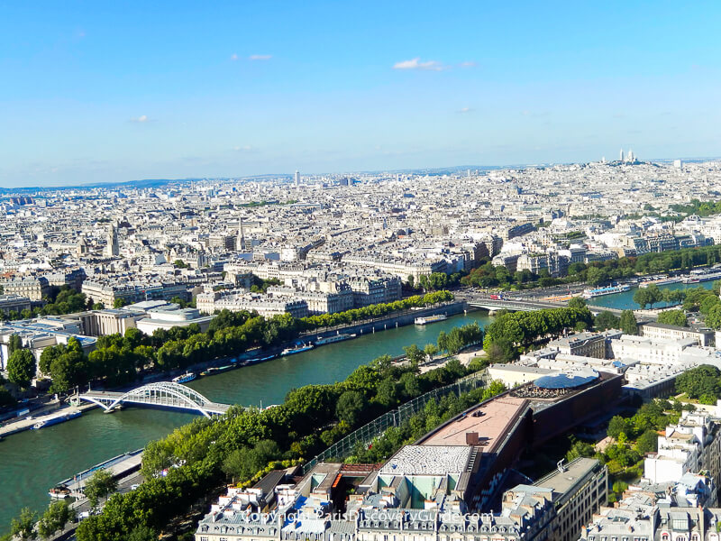 Paris skyline seen from the Eiffel Tower's Second Level observation deck, with Pont Debilly bridge and other nearby attractions easy to spot and Sacre Coeur and Montmartre visible on the skyline
