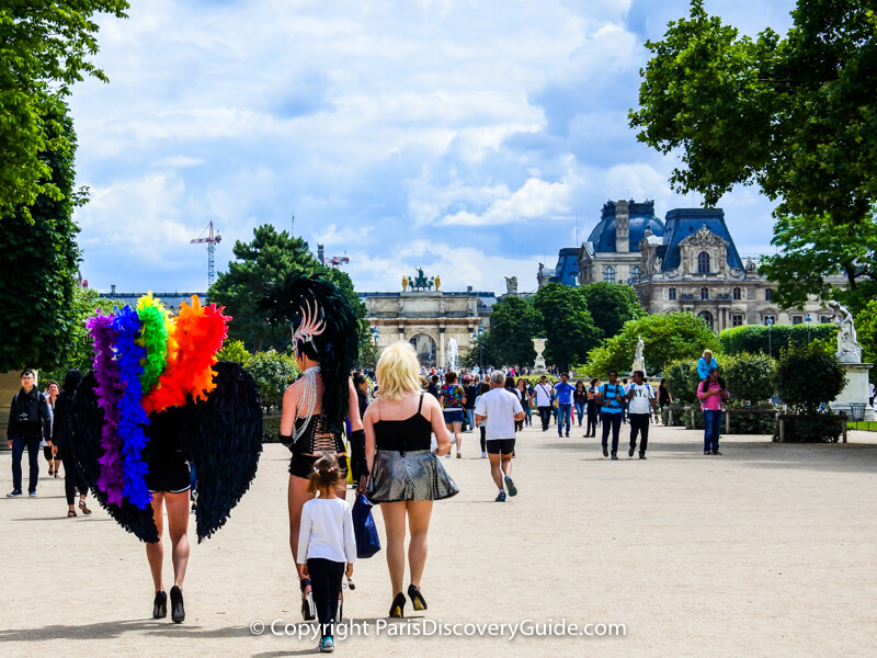 Participants in Paris Pride Parade walking in Tuileries Garden