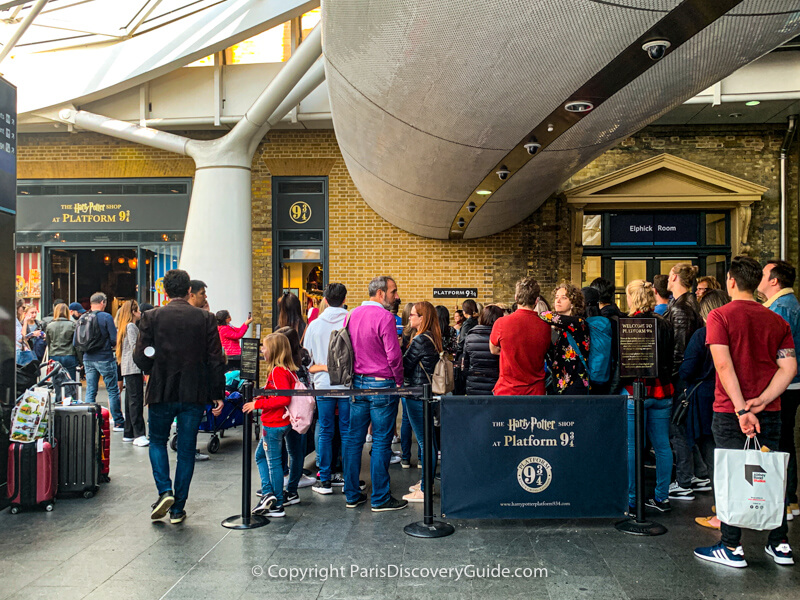 Harry Potter fans wait in line to take photos at Platform 9 3/4 in King's Cross Station
