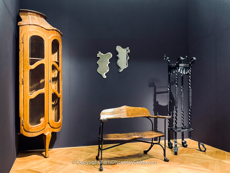Corner display cabinet, church bench, mirrors. and wrought iron garden pot holder designed by Spanish architect Antoni Gaudí