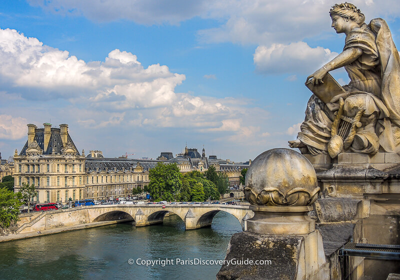 Giant statue perched on the edge of the Summer Terrace overlooking the Seine River, Pont Royal, and the Louvre