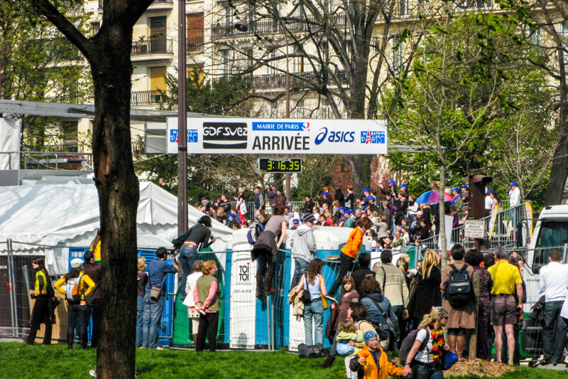 Spectators waiting behind barriers (and port-a-potties) at the Paris Marathon Finish Line
