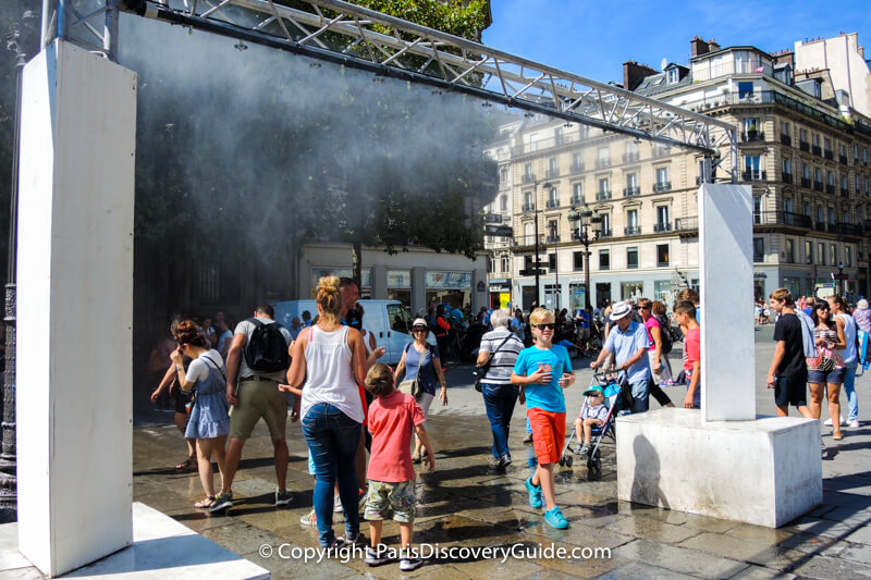 """Shoppers from nearby rue de Rivoli walk over to cool off under the mist fountain - another popular feature at the Paris City Hall """"beach"""""""