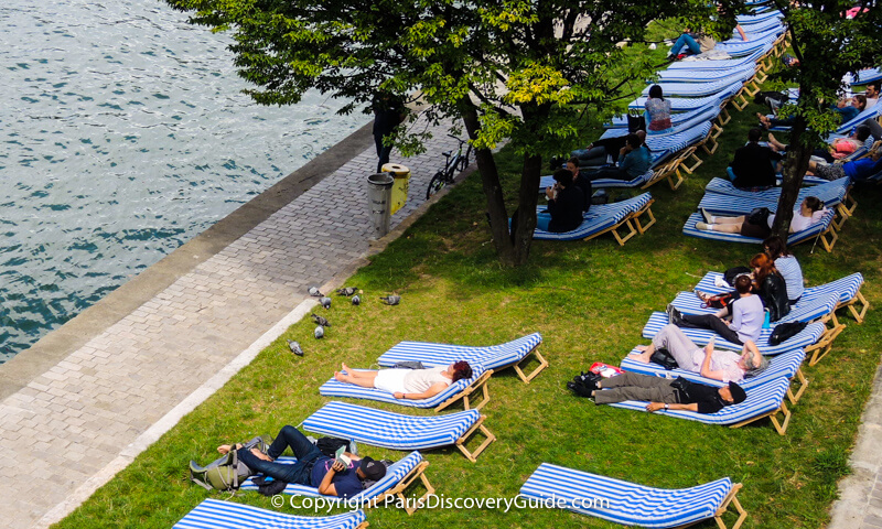 """Relaxing on a grassy Paris """"beach"""" overlooking the Seine River"""