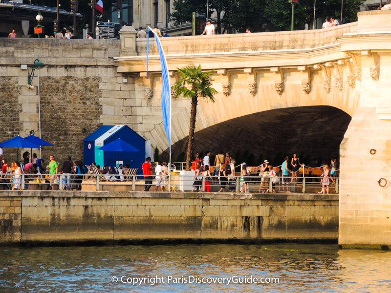 Palm tree, beach umbrellas, and striped beach chairs next to the Pont Neuf Bridge at Paris Plages