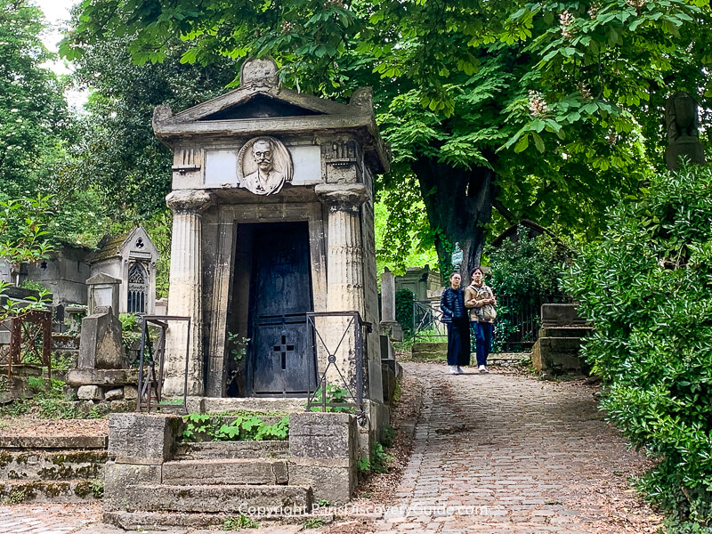 Couple walking along path atPere Lachaise Cemetery