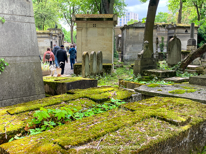 Moss-covered graves at Pere Lachaise Cemetery