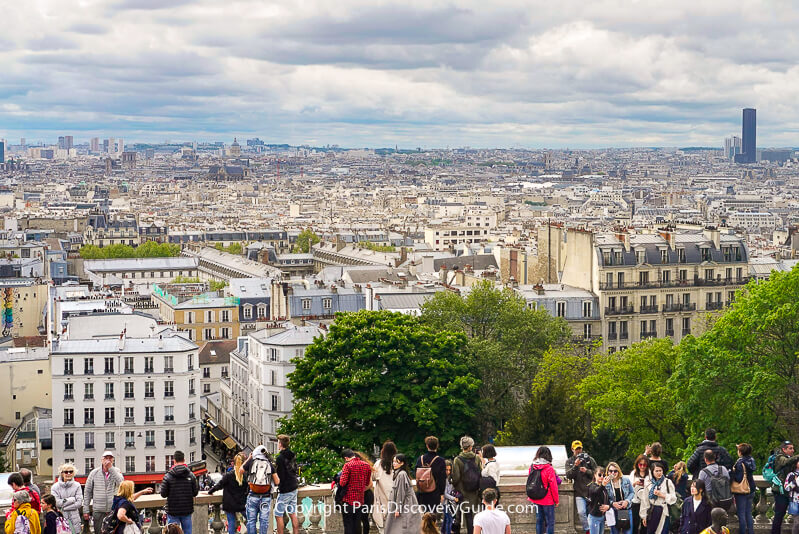 Sacre Coeur visitors on the terrace overlooking the Paris skyline