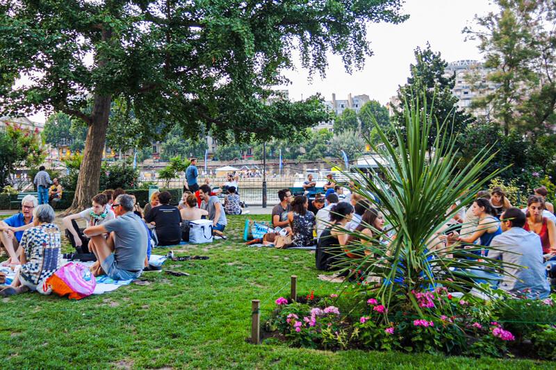 Parisians relaxing on Square de Vert-Galant overlooking the Seine River near Sainte Chapelle