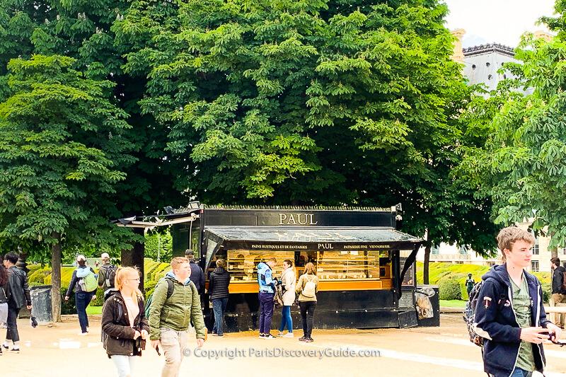 Shoppers strolling along Avenue des Champs Elysées' broad sidewalk lined by horse chestnut trees