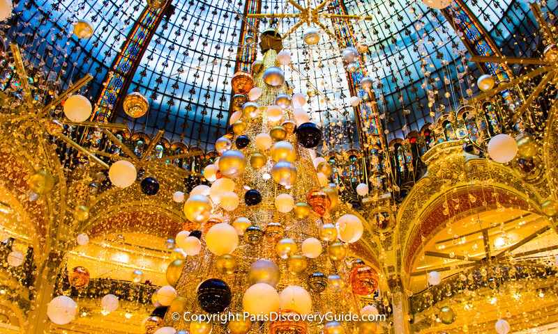 christmas decorations and lights suspsended from the skylight dome in galeries lafayette
