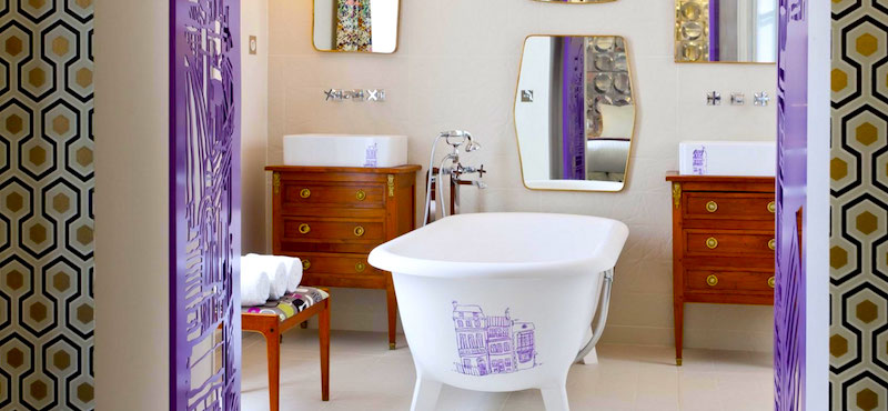 Vibrant graphic design meets antique furnishings in this Hôtel Crayon bathroom in Paris's 1st Arrondissement