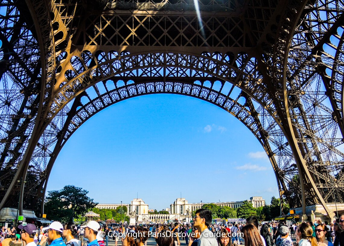 "During summer months, crowds waiting in Eiffel Tower ticket lines fill all the space around the ""Iron Lady"""