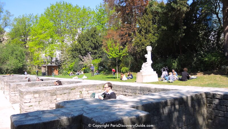 Grassy picnic area and seating alcoves along the stage of Arènes de Lutèce in Paris