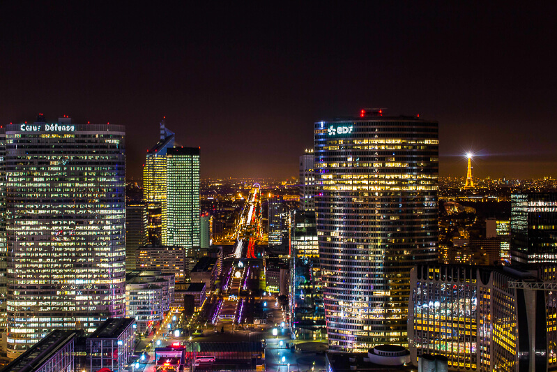 View from Grande Arche at night showing La Defense skyline and Paris skyline, including Arc de Triomphe and Eiffel Tower - Photo credit: subterranologie.com, CC A-SA4.0