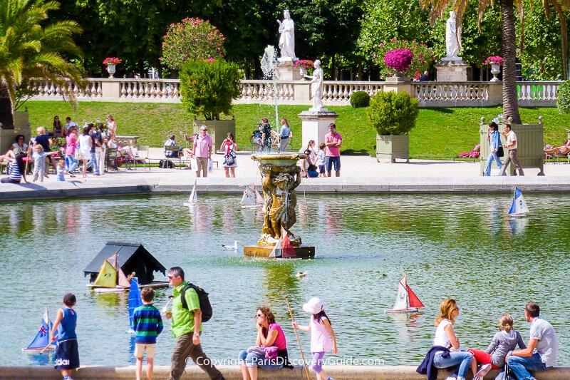 "Children ""sailing"" wooden boats in Luxembourg Garden"