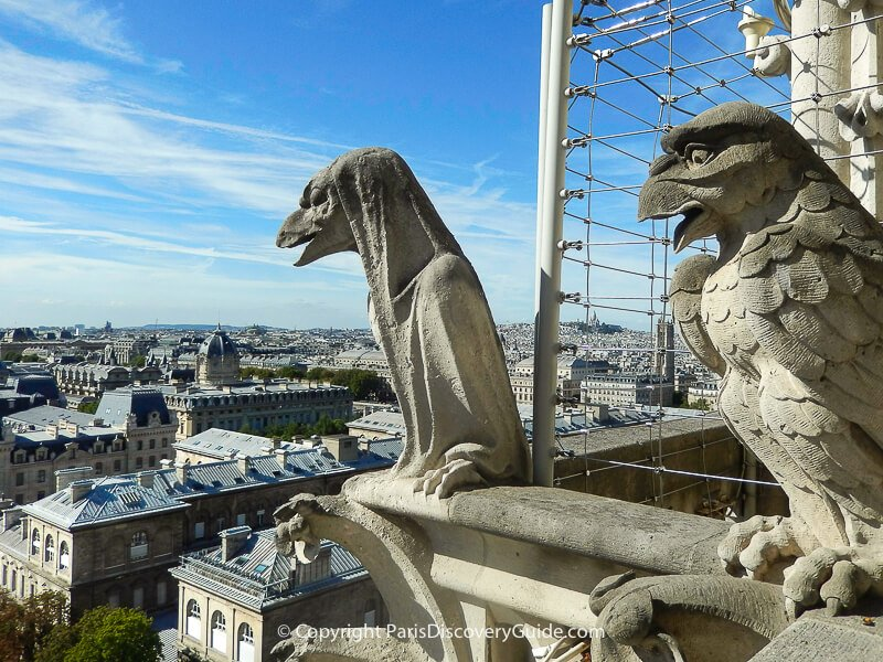Gorgoyles peering out over the rooftops of Paris, with Sacre Coeur visible on the skyline