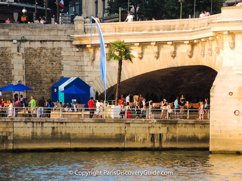 Palm tree, beach umbrellas, and striped beach chairs next to the Pont Neuf Bridge at Paris Plages