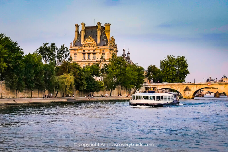 Seine River cruise boat heading toward Pont Royal bridge