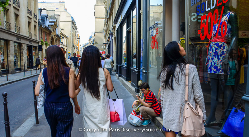 Soldes (sales) signs for 50% off in boutiques along rue de Franc Bourgeois in the Marais neighborhood in Paris