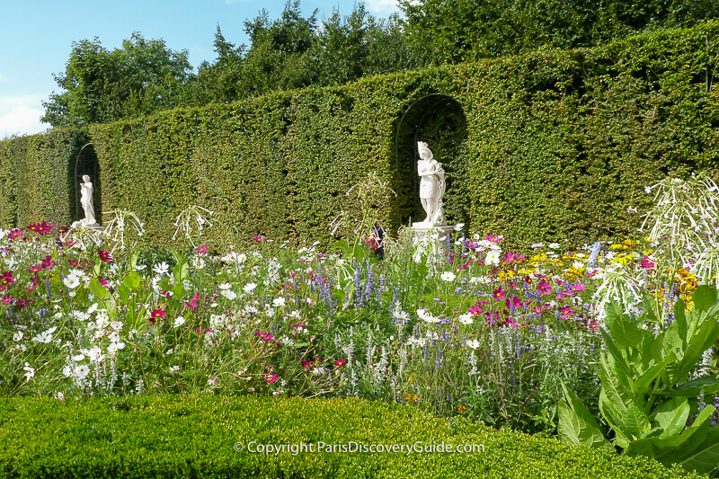 Statues in the walls of a Grove overlooking summer flowers at Versailles Gardens