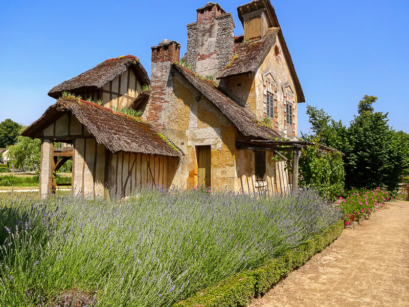 The rustic Flemish-style mill house (the mill wheel is on the other side) and lavender garden in Marie Antoinette's Hamlet in the park of the Château de Versailles - Photo credit: Alexandre Breveglieri