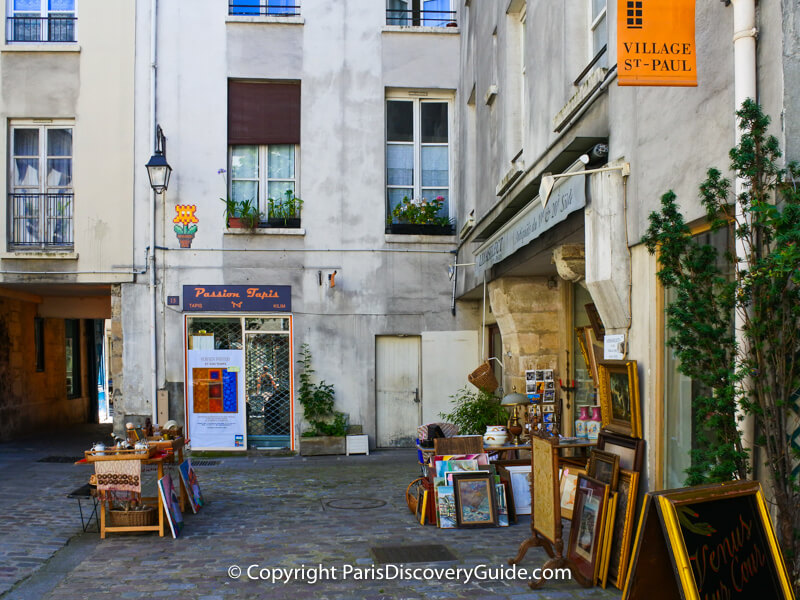 Shops featuring rugs and 19th and 20th century antiques in Village Saint-Paul in Paris