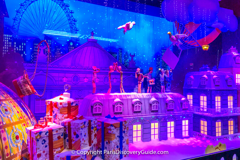 A pigeon and a dove embark on a magical journey as animated doll figures play musical instruments and dance on a Parisian rooftop with a giant ferris wheel and a hot air balloon in the background - part of a multi-window scene at Galeries Lafayette